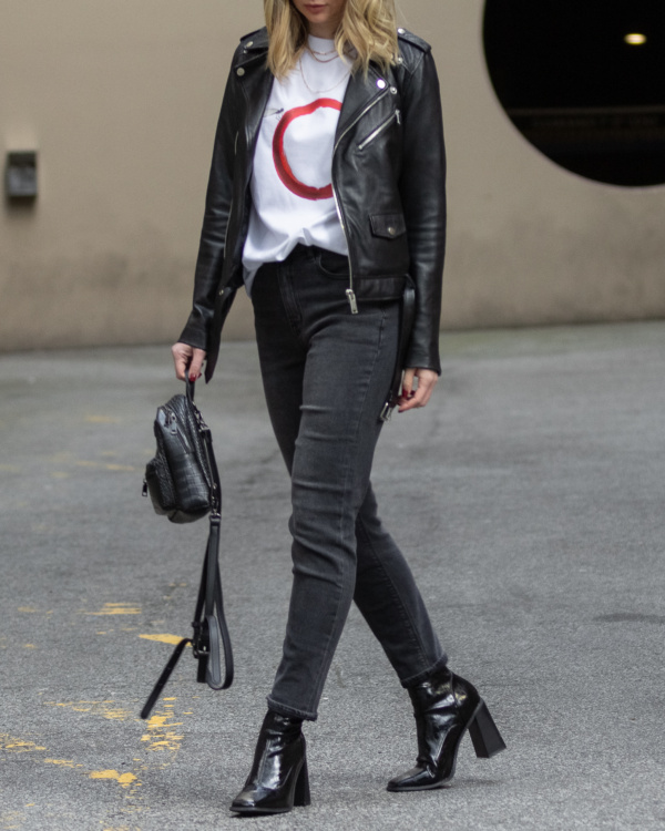 Model wearing black boots, black jeans, a leather jacket and The Dragonfly tshirt from The Foreign Sun.