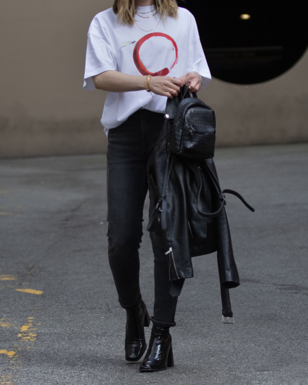 Girl wearing a white oversized tshirt with a dragonfly print from The Foreign Sun.
