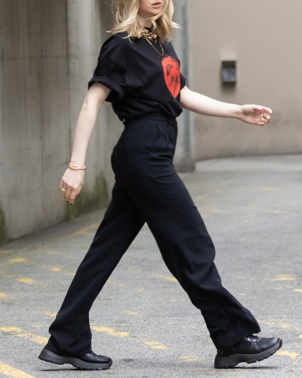 Girl wearing a black oversized tshirt with rolled sleeves and tucked in.