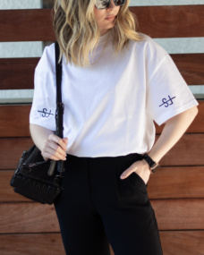 Girl wearing the white sleeve logo tshirt from The Foreign Sun