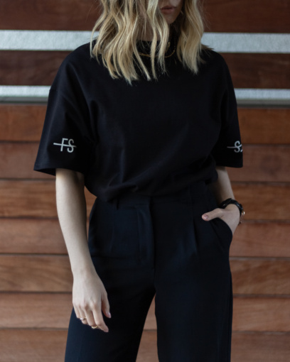 Model wearing the sleeve logo black tshirt tucked in black dress pants.
