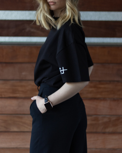 Model wearing the sleeve logo black tshirt from The Foreign Sun tucked in black dress pants.